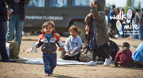 young refugee child walking in a refugee camp